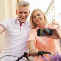 Loving mature couple taking selfie with bike
