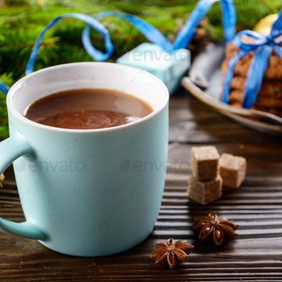 Christmas background of blue hot chocolate mug, spruce branch an