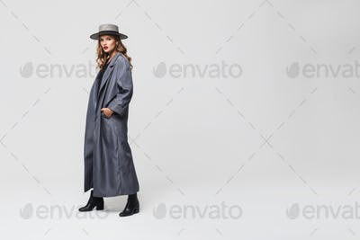 Young attractive woman in hat and cloak holding hands in pockets thoughtfully looking in camera