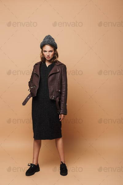 Young beautiful serious woman in hat, leather jacket and black dress angrily looking in camera