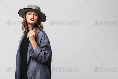 Young beautiful woman with wavy hair in modern hat and cloak thoughtfully looking aside