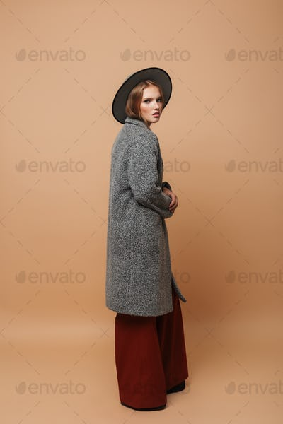 Young beautiful pensive woman with hat in gray coat and wide pants thoughtfully looking in camera
