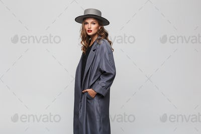 Young gorgeous woman with wavy hair and red lips in hat and cloak holding hands in pockets