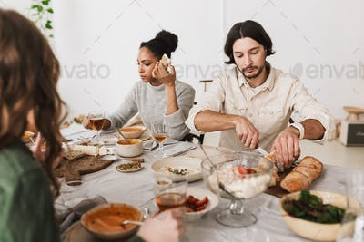 Thoughtful man and beard sitting at the table cutting bread while afro american woman eating