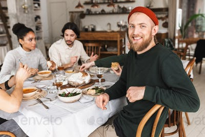 Joyful man in red knitted hat with beard sitting at the table happily looking in camera