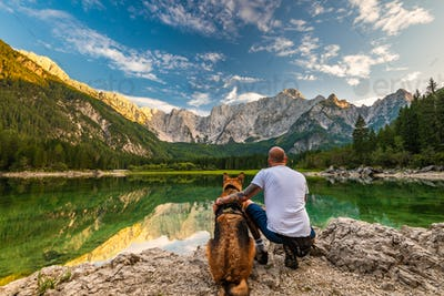 Tattoed Man with Dog Looking at Beautiful Lake and Mountains. Ou