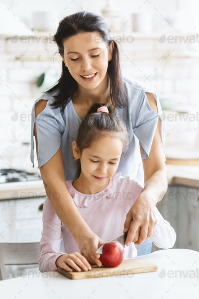 Mother Teaching Her Little Daughter To Cut Apple With Knife