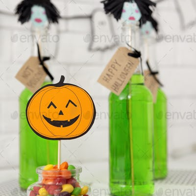 Trick or treat candies and green cocktails in bottles