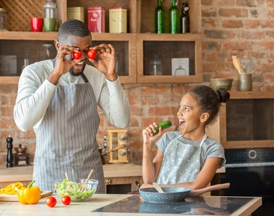Funny daddy and daughter having good time at kitchen