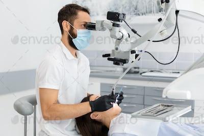 Professional dentist using modern technologies in treatment