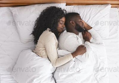 Romantic black couple hugging while sleeping in bed
