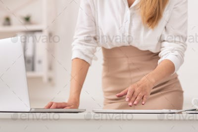 Unrecognizable Businesswoman Using Tablet And Laptop Standing In Office