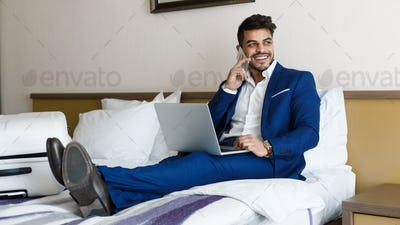 Happy businessman sitting on hotel bed, working with laptop