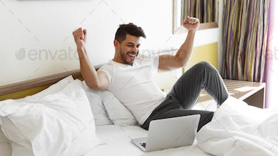Young man celebrating success, sitting on bed, using laptop