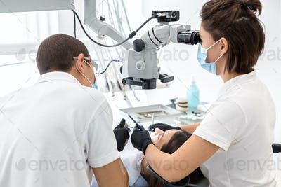 Back view of dentist doctors making dental cleaning