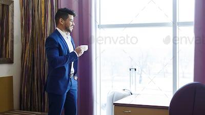 Handsome man in suit drinking coffee near window in hotel