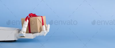 Gift box in automated robot hand, blue background