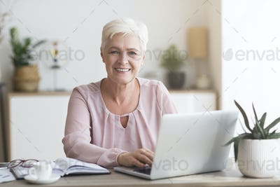 Happy business lady working with laptop at home