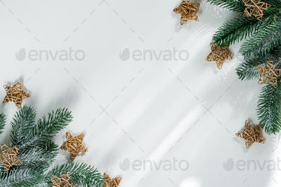 Fir tree branch with gold wooden stars on white paper, top view copy space