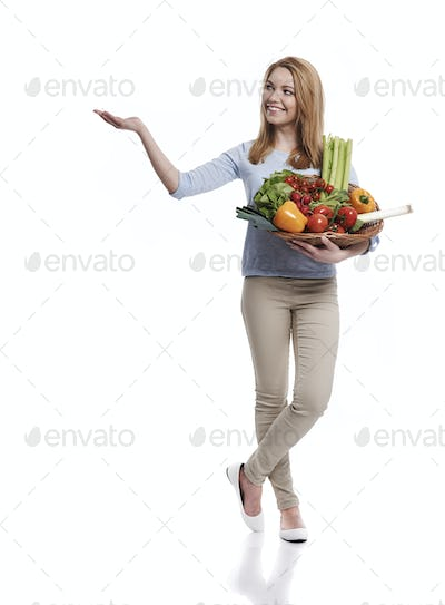 Woman with basket full of healthy food showing on copy space