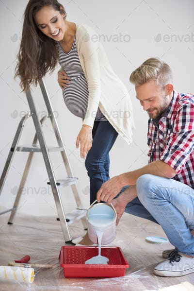 Wife helping his husband with painting baby's room