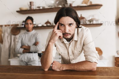 Young international couple in quarrel spending time in kitchen at home
