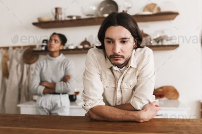 Upset man with beard leaning on table thoughtfully looking aside with sad african american woman