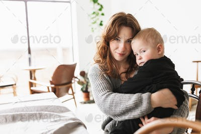 Young beautiful woman in knitted sweater hugging her little son dreamily looking in camera together
