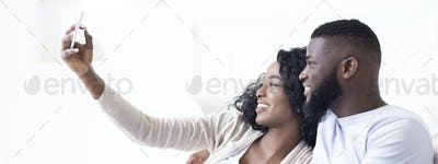 Smiling family couple taking self-photograph on smartphone