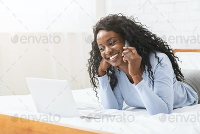 Woman laying on bed in front of laptop, using cellphone