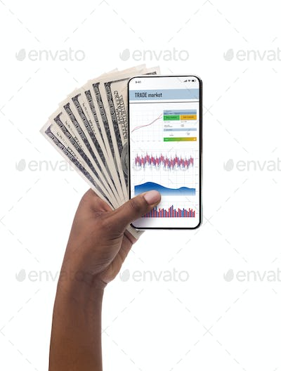 Female hand holding smartphone with opened trading app and cash