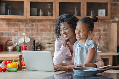Mommy and daughter reading recipe on laptop at kitchen