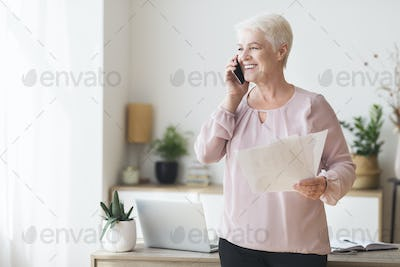 Aged business consultant talking by phone with clients