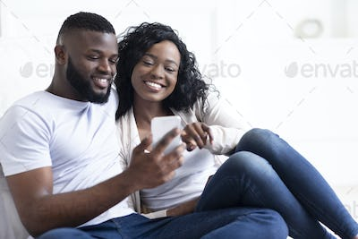 Happy African American couple using smartphone, surfing internet at home