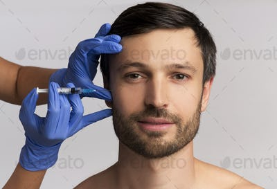 Portrait Of Middle-Aged Man Receiving Wrinkle-Removing Injection, White Background