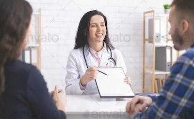 Friendly family doctor explaining prescription to patients at clinic