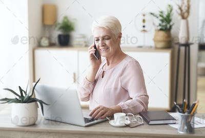 Ambitious elderly business woman working from home
