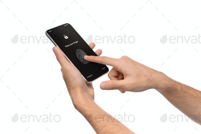 Man's hands using fingerprint scanning app on cellphone screen