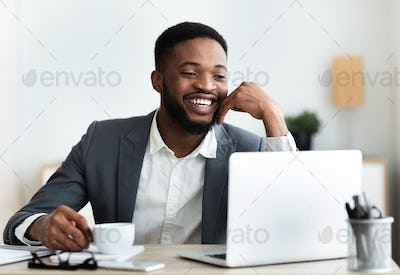 Cheerful african american employee sitting at workplace in modern office