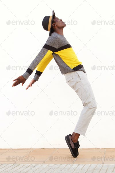 Full length african male dancer standing on his tip toes making a cool dance pose