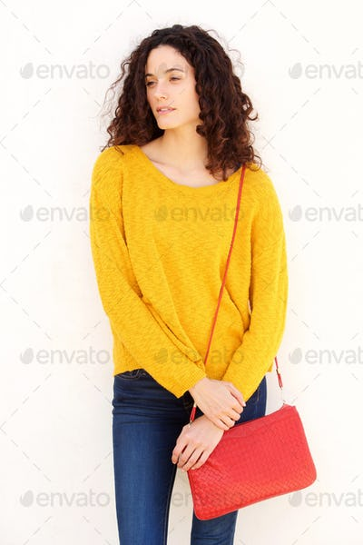 female fashion model with purse against white background
