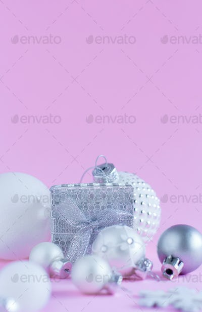Silver Christmas baubles and gift box on a light pink background