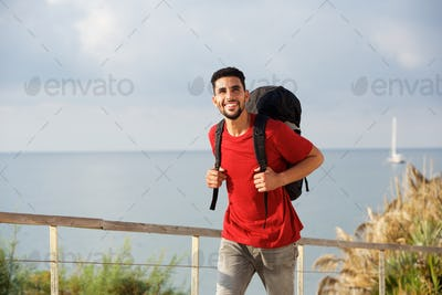 happy young man walking with backpack by the sea