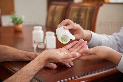 Crop doctor pouring pills in hand of patient