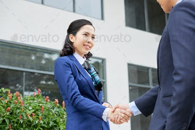 Smiling Asian woman shaking hand of colleague