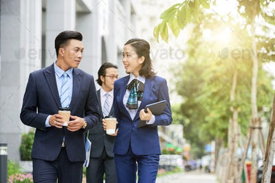 Stylish Asian businesspeople with coffee walking on street