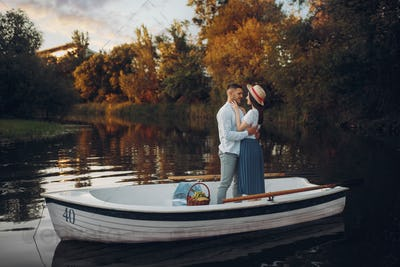 Lovers hugs in a boat on quiet lake at summer day