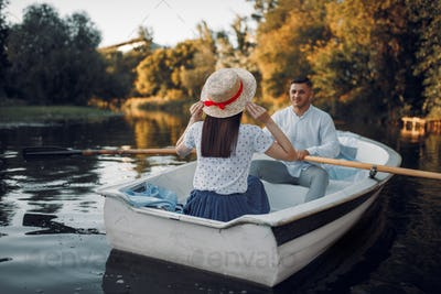 Love couple boating on lake at summer day