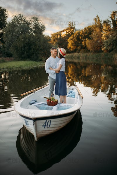 Love couple standing in a boat on quiet lake