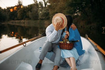 Love couple kissing in a boat on lake at sunset